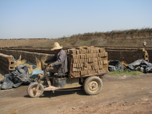 "Transporting bricks from the ""factory"" to dry in the sun in Pangliu Village"