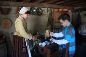A student helps prepare food at Plimoth Plantation