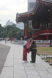 A Japanese couple take a selfie at a Buddhist temple