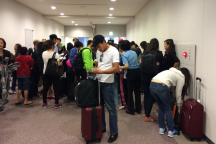 This is how they let people know about transfer flights -- by crowding around paper print outs?