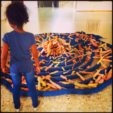 A small museum visitor looking at an exhibit of doll legs and rope.